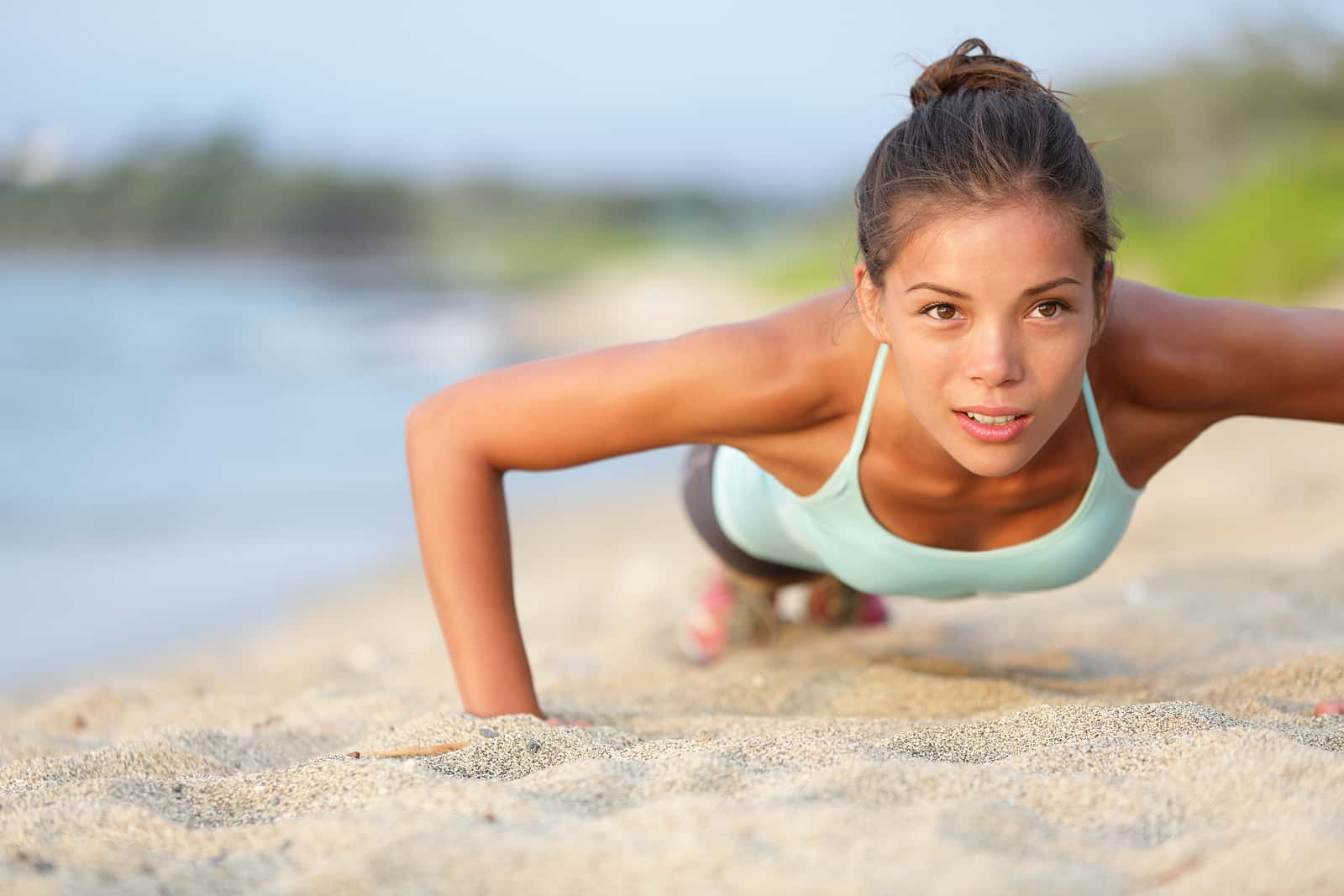 Push-ups fitness woman doing pushups outside on beach