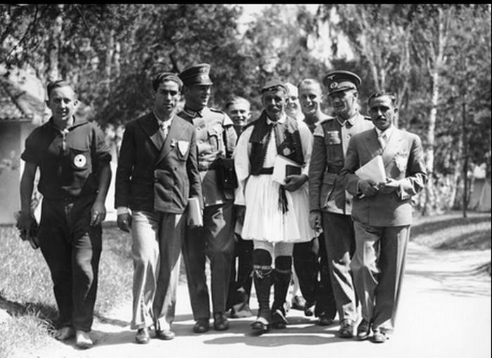 Μέλη της ελληνικής αποστολής και Γερμανοί αστυνομικοί συνοδεύουν τον Σπύρο λούη στο Ολυμπιακό Χωριό του Βερολίνου.