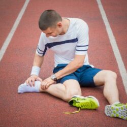 an-athlete-examines-his-painful-heel